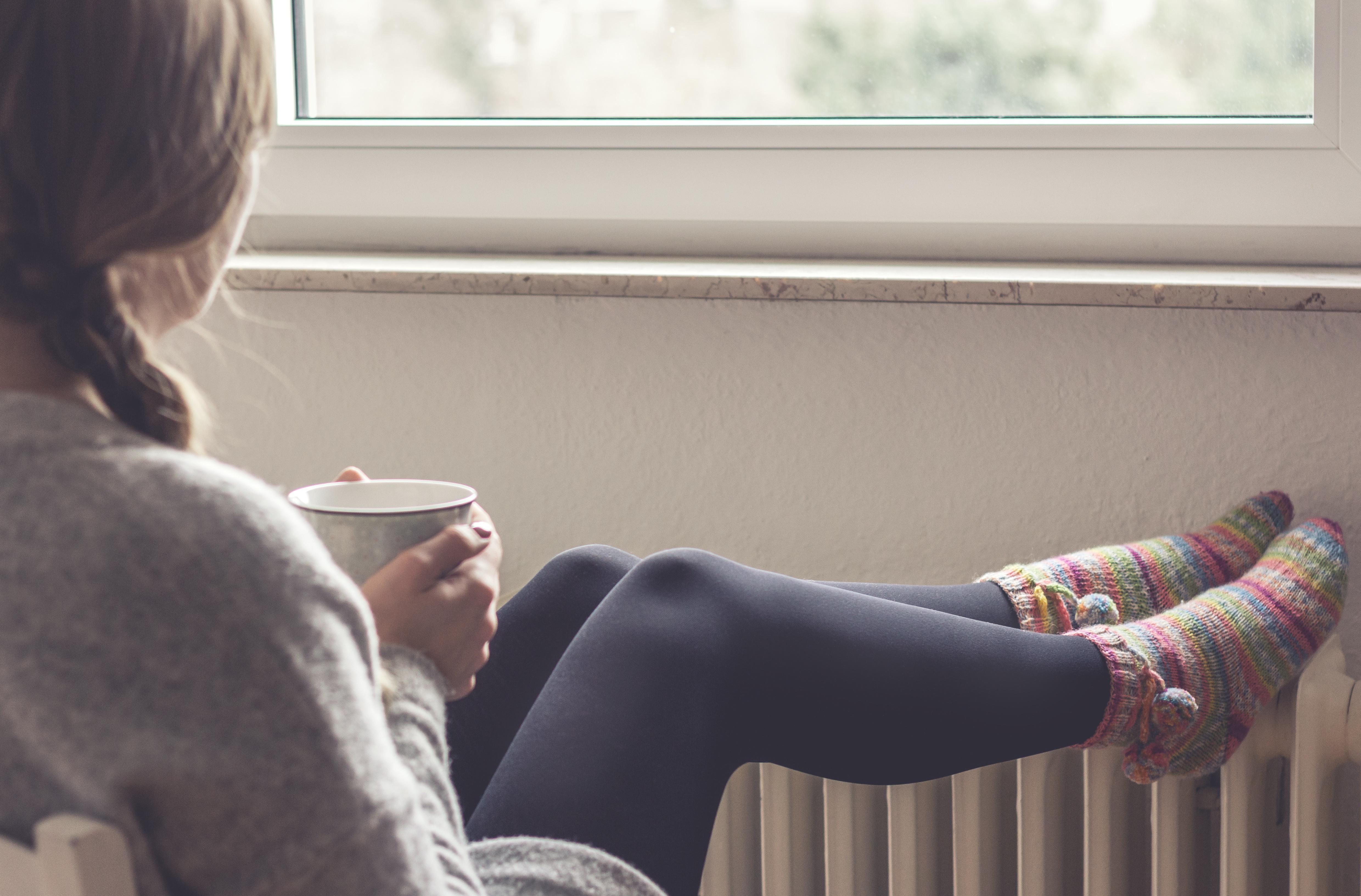 Junge Frau schaut aus dem Fenster, trinkt Tee und legt Füße zum Aufwärmen auf die Heizung.